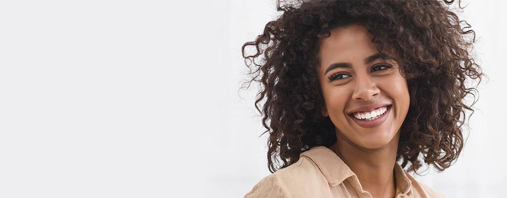 Frau strahlt mit weißen Zähnen als Symbol für Bleaching