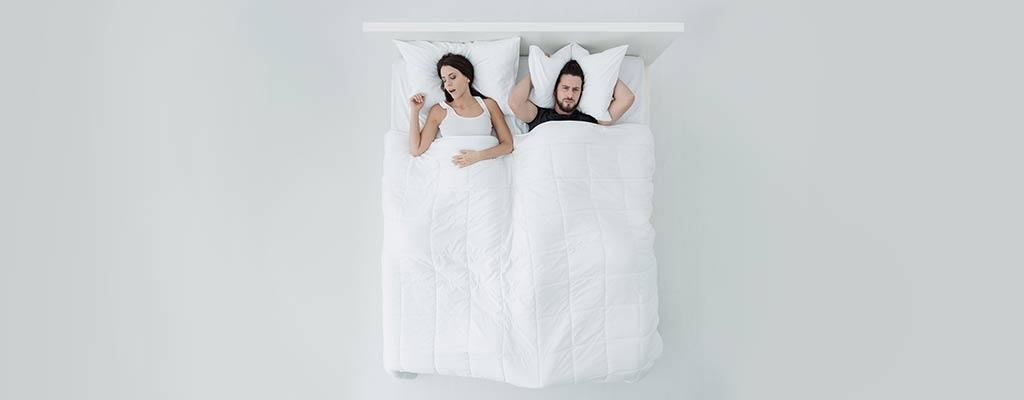 Partner liegt wach im Bett, weil die Partnerin laut schnarcht
